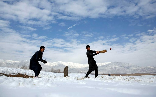 Afghan men play cricket on a field covered in snow on the outskirts of Kabul, Afghanistan Dec 16, 2017. REUTERS/Mohammad Ismail