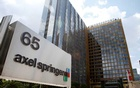 The logo of German publisher Axel Springer is pictured in front of the company's headquarters in Berlin July 25, 2013. REUTERS/Fabrizio Bensch/File Photo