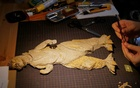 A cardboard sculpture of Godzilla is seen on the desk of 29-year-old artist Monami Ohno in Tokyo, Japan August 25, 2021. Picture taken August 25, 2021. REUTERS/Joseph Campbell