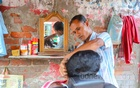 Hairdresser Uttam Das has opened a makeshift shop on the footpath of DIT Avenue in Dhaka's Motijheel after having no work for a long time due to coronavirus lockdowns. Low-income men are his clients. Photo: Asif Mahmud Ove