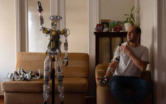 Saidullah Karimi, an orthopaedic technician from Afghanistan, demonstrating how the robot Athena functions in Athens, Greece on Aug 26, 2021. He built it largely out of items he picked out of the trash. (Loulou d'Aki/The New York Times)