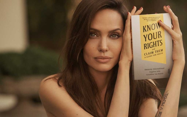 Actor Angelina Jolie poses with the book