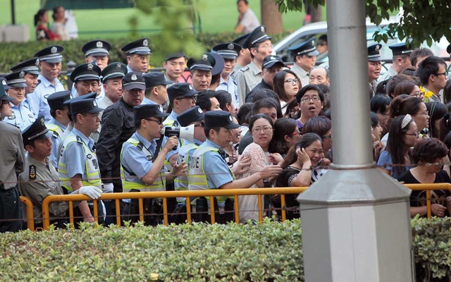 Police officers remove fans standing outside the opening ceremony of the 17th Shanghai International Film Festival, June 14, 2014. REUTERS