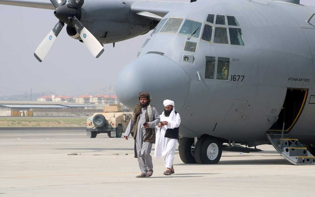 Taliban walk in front of a military airplane a day after the US troops withdrawal from Hamid Karzai International Airport in Kabul, Afghanistan August 31, 2021. REUTERS