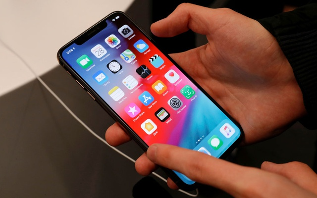 A customer tests a smartphone during the launch of the new iPhone XS and XS Max sales at
