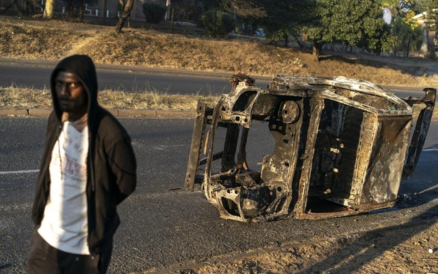 A charred vehicle in Phoenix, South Africa, where at least 20 people were allegedly killed by residents as they barricaded their neighbourhood to protect from looting, July 20, 2021. As rioting and looting swept the country this summer, Indians in the suburb of Phoenix set up roadblocks to police their streets. Dozens of Black people passing through wound up dead. (Joao Silva/The New York Times