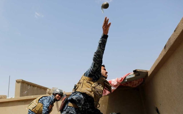 A member of the Iraqi Federal Police throws a hand grenade during clashes with the Islamic State fighters in western Mosul, Iraq, April 29, 2017. REUTERS/Danish Siddiqui/File Photo