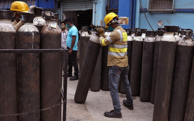Workers load empty oxygen cylinders onto a supply truck for refilling, at the Medical College and Hospital, amid the spread of the coronavirus disease (COVID-19), in Kolkata, India, May 5, 2021. REUTERS