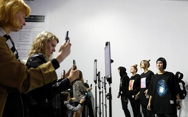 People use their smartphones to see the virtual animation on creations as they visit a presentation of the collection of partially virtual clothing with elements of augmented reality designed by FINCH brand during Ukrainian Fashion Week in Kyiv, Ukraine September 4, 2021. REUTERS/Valentyn Ogirenko