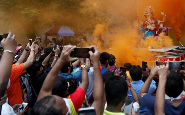 Devotees flock to catch a glimpse of an idol of the Hindu God Ganesh, the deity of prosperity, as it leaves a workshop ahead of the Ganesh Chaturthi festival in Mumbai, India, September 5, 2021. REUTERS/Francis Mascarenhas