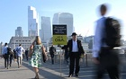 Workers pass by a sales person as they walk towards the City of London financial district as they cross London Bridge during the morning rush hour in London, Britain, September 8, 2021. REUTERS