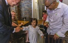 Rep Tom Suozzi,left, greets the children of Mohammad Wali, right, at his restaurant in Manhattan on Sept 8, 2021.The New York Times