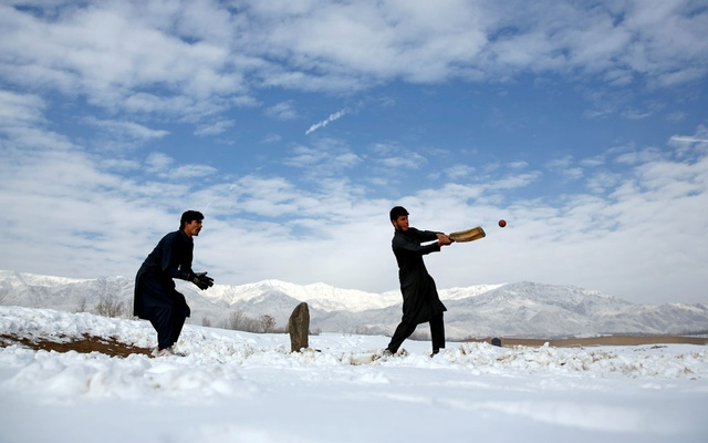 Afghan men play cricket on a field covered in snow on the outskirts of Kabul, Afghanistan December 16, 2017.REUTERS/Mohammad Ismail/File Photo