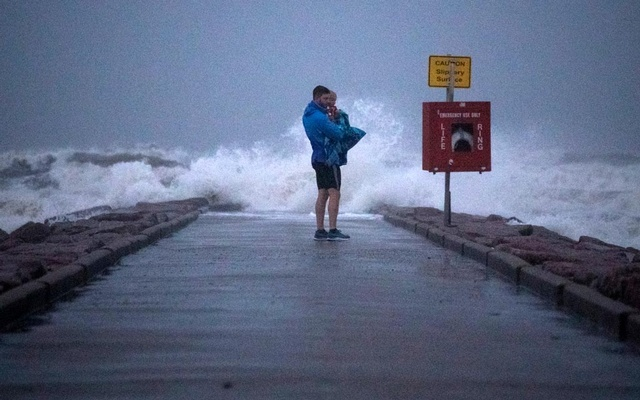 Local resident John Smith holds his 18-month-old son Owen as he stands near breaking waves on a pier ahead of the arrival of Tropical Storm Nicholas in Galveston, Texas, US, September 13, 2021. REUTERS