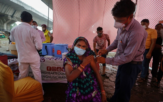 A woman receives a dose of COVAXIN coronavirus disease (COVID-19) vaccine manufactured by Bharat Biotech, during a vaccination drive organised by SEEDS, an NGO which normally specialise in providing relief after floods and other natural disasters, at an under-construction flyover in New Delhi, India, August 31, 2021. Reuters