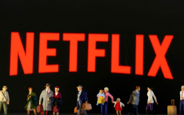 Small toy figures are seen in front of displayed Netflix logo in this illustration taken March 19, 2020. REUTERS