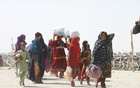 People from Afghanistan walk with their belongings as they cross into Pakistan at the 'Friendship Gate' crossing point, in the Pakistan-Afghanistan border town of Chaman, Pakistan, September 7, 2021. REUTERS/Saeed Ali Achakzai