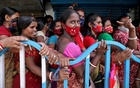 Women wait to receive a dose of COVISHIELD vaccine, a coronavirus disease (COVID-19) vaccine manufactured by Serum Institute of India, outside a vaccination centre in Kolkata, India, August 31, 2021. REUTERS