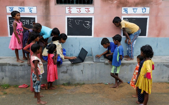 Children, who do not have access to internet facilities and gadgets, use laptops in an open-air class outside a house with the walls converted into black boards following the closure of their schools due to the coronavirus disease (COVID-19) outbreak, at Joba Attpara village in Paschim Bardhaman district in the eastern state of West Bengal, India, September 13, 2021. REUTERS/Rupak De Chowdhuri