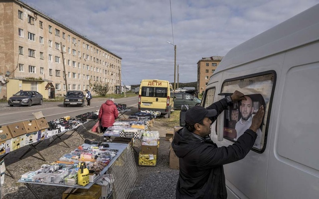 An entrepreneur puts up a poster of a friend running for elected office on his van in Teriberka, an Arctic village near Murmansk, Russia, Aug 26, 2021. Ahead of Russia's parliamentary election this weekend, President Vladimir Putin's rule has reached a new apogee of authoritarianism, coated in a patina of comfortable stability. Sergey Ponomarev/The New York Times