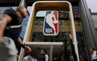 The NBA logo is displayed as people pass by the NBA Store in New York City, US, October 7, 2019. REUTERS/Brendan McDermid
