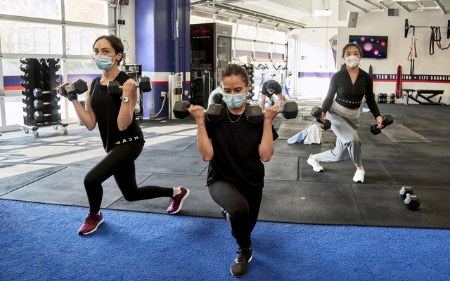 People wear face masks while exercising at F45 Training Arts District, a gym in Los Angeles, on Aug. 16, 2021. Cities and large parts of the economy continued to bounce back this year, as if returning to some sense of normalcy. But when the pandemic's path veered, so did our sense of where the finish line was. Philip Cheung/The New York Times