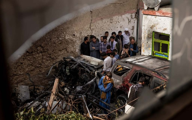 People gather near remnants of a vehicle destroyed by a US drone strike that occurred a day earlier, in Kabul, Afghanistan on Monday, Aug 30, 2021. Jim Huylebroek/The New York Times