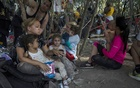A group of migrants from Venezuela seeking asylum rest in the shade near the Del Rio International Bridge before turning themselves in to Border Patrol agents in Del Rio, Texas on Friday, Sept 17, 2021. The New York Times