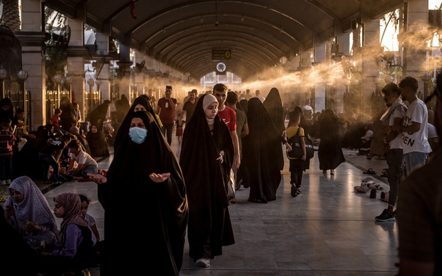 Pilgrims take shelter from the heat under water sprays at the Imam Hussain shrine in Karbala, Iraq, on July 23, 2021. Militia violence has driven antigovernment protesters underground and shaken Karbala, a city of gold-domed Shiite shrines. Sergey Ponomarev/The New York Times