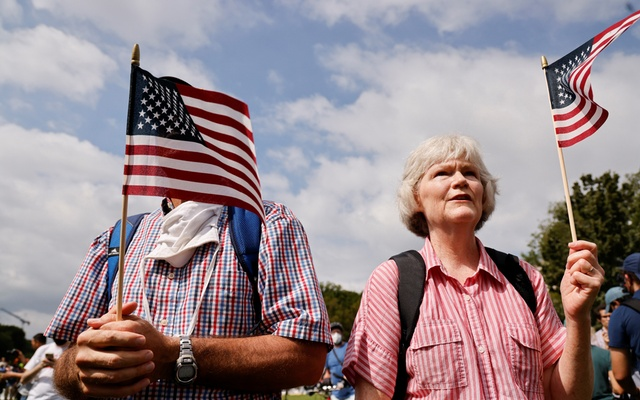 Supporters of defendants being prosecuted in the January 6 attack on the US Capitol hold US flags during a rally in Washington, DC, US, September 18, 2021. REUTERS