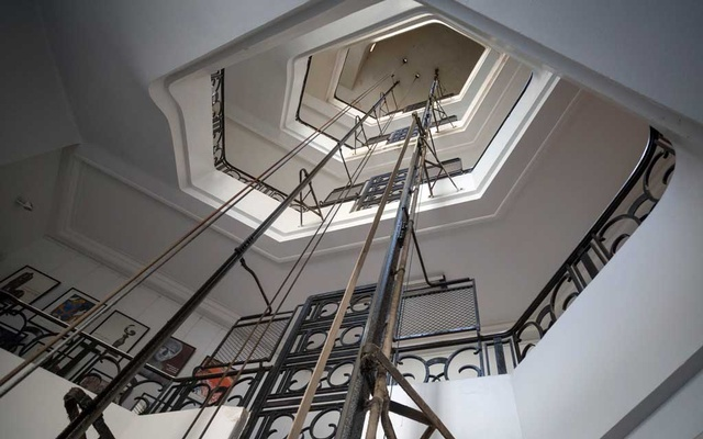 Rails and cables of a Schindler elevator ascend the floors of a 1920 art deco building in the Zamalek neighbourhood of Cairo, Aug 28, 2021. The city's geriatric lifts, graceful fin-de-siècle and Art Deco pieces from the era when the city competed with London and Paris for wealth and glamour, have been going up and down the same buildings for, in some cases, more than a century. Sima Diab/The New York Times