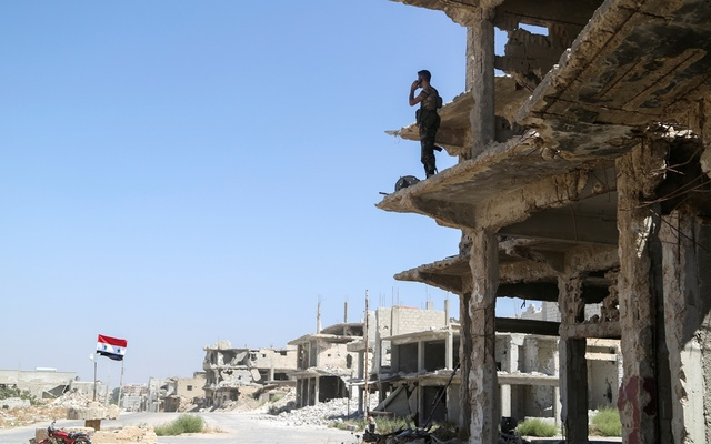 A Syrian army soldier stands on a damaged building in Deraa al Balaad, Syria, September 9, 2021. REUTERS