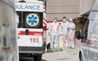 Medical personnel stand next to ambulances with COVID-19 patients as they wait in the queue at a hospital for people infected with coronavirus disease in Kyiv, Ukraine March 30, 2021. REUTERS/Gleb Garanich