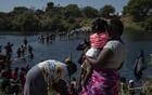 """People seeking asylum are seen crossing the Rio Grande into Del Rio, Texas on Friday, Sept 17, 2021. Haiti migration officials have asked the United States for a """"humanitarian moratorium"""" even as they prepare to receive the first returnees from Texas. """"Will we have enough to feed these people?"""" (Verónica G. Cárdenas/The New York Times)"""