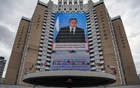 A photo of President Vladimir Putin is displayed on a monitor on the side of a hotel on the outskirts of Moscow during his annual address on April 21, 2021. Early results in Russia's parliamentary elections showed a rise in opposition to President Putin's governing party, though it was nevertheless expected to cruise easily to victory. (Sergey Ponomarev/The New York Times)