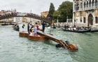 """A string quartet plays Vivaldi's """"Four Seasons from atop artist Livio De Marchi's conception, an enormous motorised watercraft called Noah's Violin, as it floats along the Grand Canal of Venice, Italy, with an escort of gondolas, Sept 18, 2021. The New York Times"""