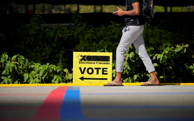 A man walks by an Elections Canada sign at a polling station during Canada's federal election, in Toronto, Ontario, Canada September 20, 2021. REUTERS