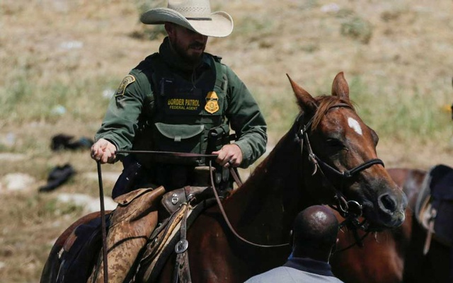 A US law enforcement officer on horseback blocks the way to a migrant wading in the Rio Grande trying to return to the United States after buying food in Mexico, as seen from Ciudad Acuna, Mexico September 19, 2021. Picture taken September 19, 2021. REUTERS/Daniel Becerril