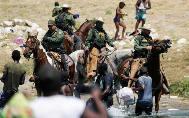 US law enforcement officers on horseback block the way to migrants reaching the shores of the Rio Grande as they try to return to the United States after buying food in Mexico, as seen from Ciudad Acuna, Mexico September 19, 2021. Picture taken September 19, 2021. REUTERS/Daniel Becerril