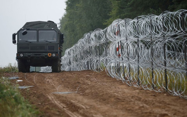 A view of a vehicle next to a fence built by Polish soldiers on the border between Poland and Belarus near the village of Nomiki, Poland Aug 26, 2021. REUTERS/Kacper Pempel