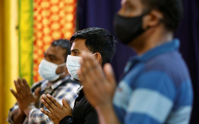 Migrant workers pray at a temple, before enjoying time off at Little India, as part of a pilot programme to allow fully vaccinated migrant workers back to the community after more than a year of movement curbs due to the coronavirus disease (COVID-19) outbreak, in Singapore Sept 15, 2021. REUTERS/Edgar Su