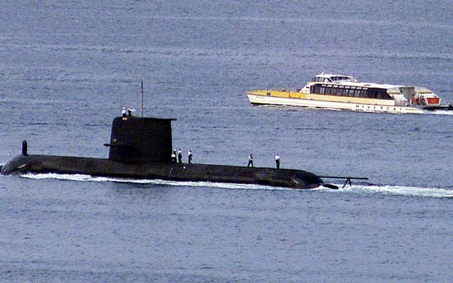 A Rivercat ferry passes by the Royal Australian Navy's Collins-class submarine HMAS Waller as it leaves Sydney Harbour on May 4, 2020.