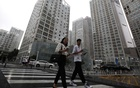 People walk past an office compound in Beijing's Central Business District (CBD), China, July 13, 2021. REUTERS