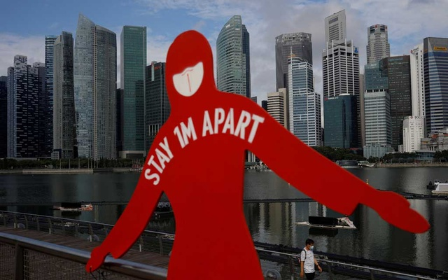 A man wearing a face mask passes a sign put up to encourage social distancing during the coronavirus disease (COVID-19) outbreak, at Marina Bay in Singapore, September 22, 2021. Reuters