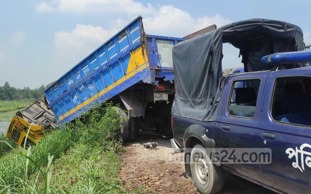 A police vehicle is seen next to the truck that plunged into a roadside ditch after a three-vehicle collision in Tangail's Kalihati on Friday, Sept 24, 2021.