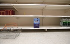A shopping basket is discarded next to empty shelves of the soft drinks aisle, in Sainsbury's supermarket in Harpenden, Britain, September 22, 2021. Reuters