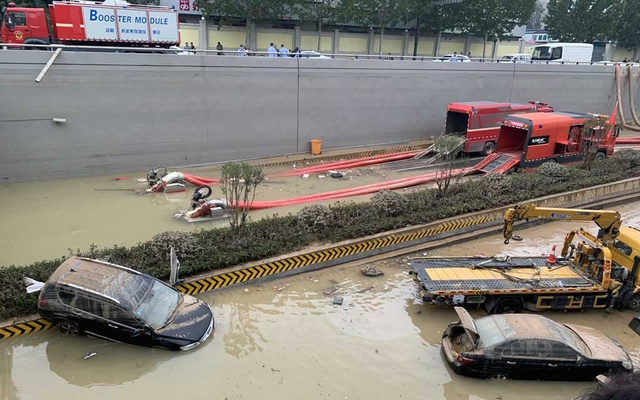 Tubes empty a flooded highway tunnel as a tow truck removes abandoned vehicles in Zhengzhou, China, July 23, 2021. At least four people died in the highway tunnel in central China that flooded at the same time as a subway tunnel after eight inches of rain fell in a single hour. The New York Times