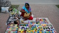Parvin Begum is selling bangles on the footpath in front of the National Parliament building in Dhaka on Monday, September 27, 2021, while taking care of her two-year-old child. Her husband, another hawker, does not earn enough by himself to allow the family to get by. Photo: Kazi Salahuddin Razu