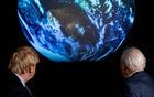 British Prime Minister Boris Johnson and David Attenborough look at a projection of planet Earth during a conference about the UK-hosted COP26 UN Climate Summit, at the Science Museum in London, Britain February 4, 2020. Chris J Ratcliffe/Pool via REUTERS