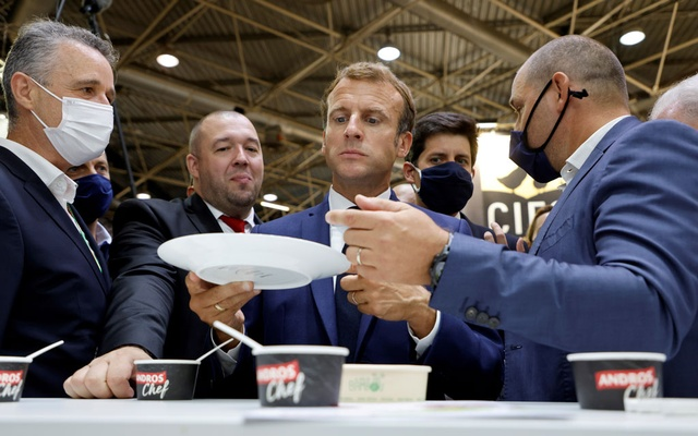 French President Emmanuel Macron and his personal representative for gastronomy Guillaume Gomez taste goods during a visit to the International Catering, Hotel and Food Trade Fair (SIRHA) at the Eurexpo hall in Lyon, France, September 27, 2021. Ludovic Marin/Pool via REUTERS